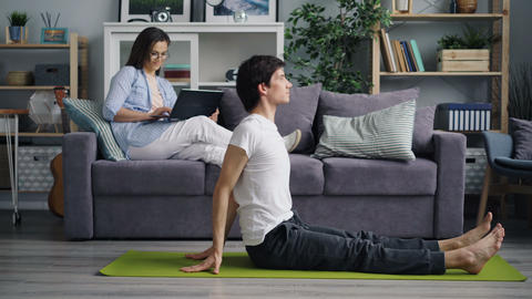 Wife checking social media using laptop while husband doing yoga working out Footage