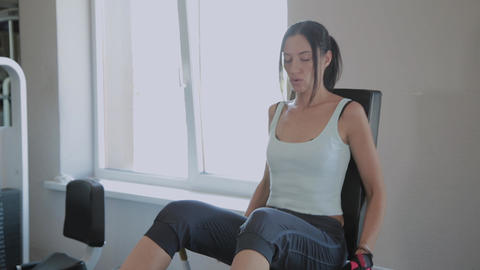 Beautiful active woman shakes legs on the gym at the gym Footage