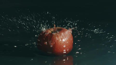 Red apple falls on shallow water surface. Slow motion, shot on Red Footage