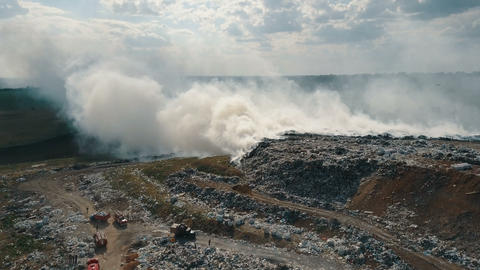 Aerial view of burning garbage dump polluting the environment. Strong wind rises Footage