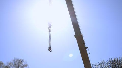 Construction crane suspended metal cables sun blue sky Live Action