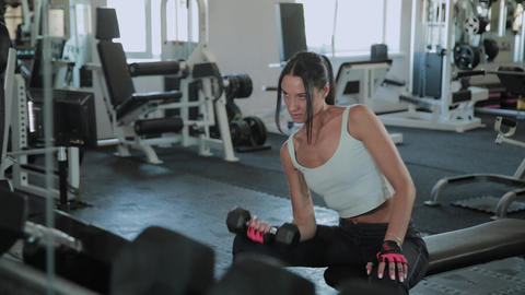 Young active girl lifts dumbbell for sitting biceps Footage