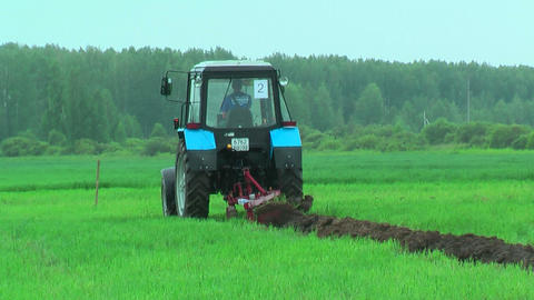 Young tractor operator plows the site in rain Footage