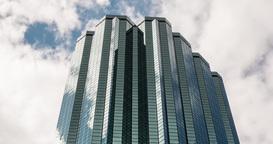 Time lapse establishing shot of glass skyscraper in modern city Footage