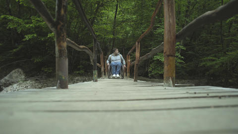 Disabled Man In Wheelchair On A Wooden Bridge Footage