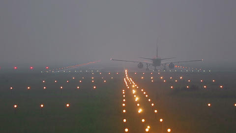 Airplane taxiing on runway in fog Footage