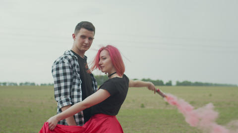 Positive couple with color smoke bomb posing in nature Footage