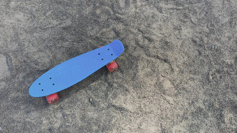 Skateboard standing on the sand in bright weather Footage
