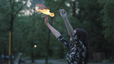 Grace beautiful girl performing a show with flame standing in front of forest Footage
