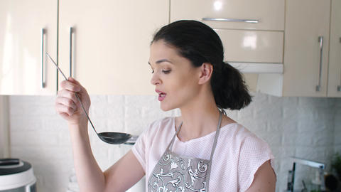 Woman tastes soup before serving Footage