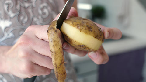 Hands peeling potatoes at kitchen Footage