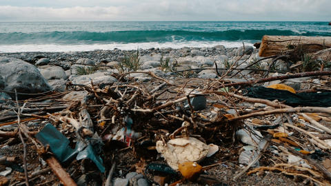 Trash, plastic, garbage, environmental pollution on the beach. Waves in slow Live Action