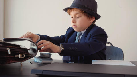 Young boy businessman trying to open briefcase on work table in office. Cute boy Live Action
