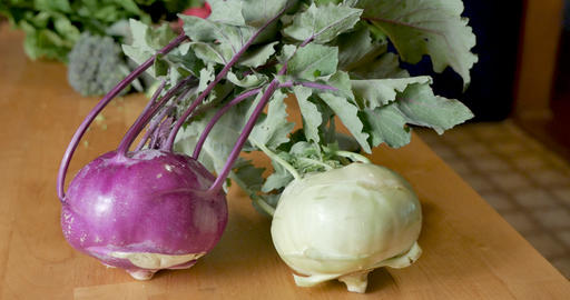 Two varieties of fresh, ripe, organic purple and white kohlrabi vegetables on a wooden cutting board GIF