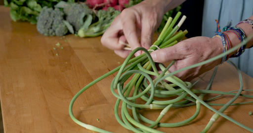 Hand removing a rubber band from a bunch of garlic scapes on a cutting board with a variety of other Footage