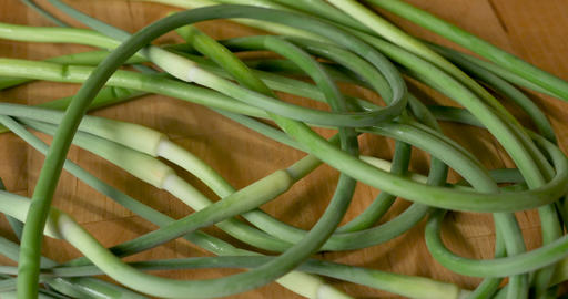 Overhead shot of a bunch of organic, fresh, seasonal, spring, garlic scapes on a wooden cutting GIF