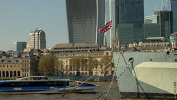A Thames river bus passes behind HMS Belfast on the River Thames Footage