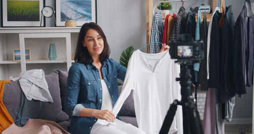 Slow motion of joyful fashion vlogger recording video describing clothes at home Footage