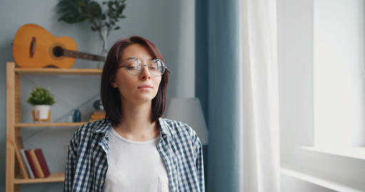 Portrait of young lady in glasses turning to camera smiling looking at camera Live Action