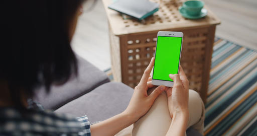Girl touching green mock-up screen of modern smartphone using device at home Footage