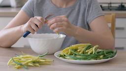 Woman is cutting the tips of green and yellow beans and preparing vegetable meal Live Action