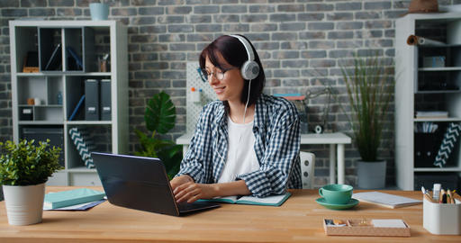 Young lady in headphones enjoying music working with laptop in office at work Footage
