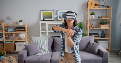 Happy girl playing game wearing virtual reality glasses in apartment alone Footage