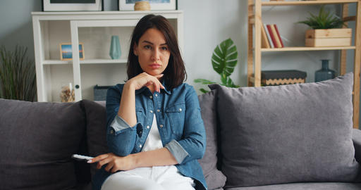 Woman student watching TV in apartment using remote control smiling having fun Footage