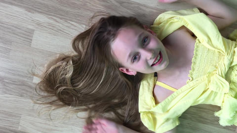 Carefree girl teenager lying down on wooden floor smiling to camera. Happy girl Live Action