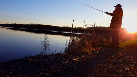 Man Fishing at Lake During Early Morning Sunrise. Person Fishing With Fishing Rod at Dawn With Sun Footage