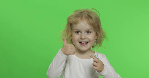 Happy little blonde girl in white t-shirt. Cute blonde child. Thumbs up Live Action