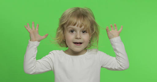 Happy little blonde girl in white t-shirt. Cute blonde child. Making faces Live Action