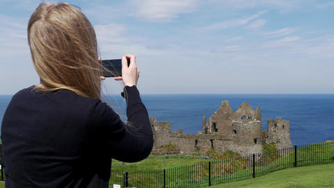 Young woman takes photos of Dunluce Castle in North Ireland Live Action