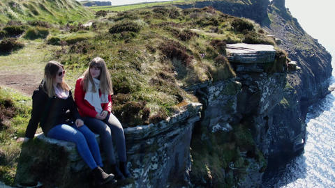 Two girls sit on the edge of the famous Cliffs of Moher in Ireland Live Action