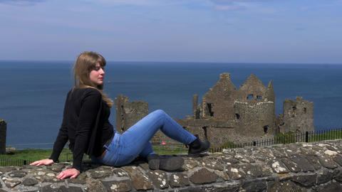 Girl relaxes on the wall at Dunluce Castle in North Ireland Footage