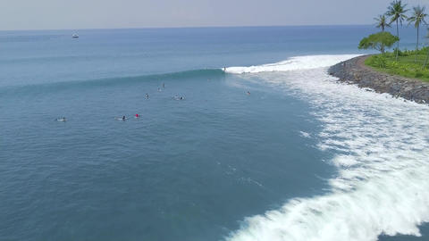 Surfing in ocean Bali island, Indonesia. Surfers surfing on surfboard on blue Live Action