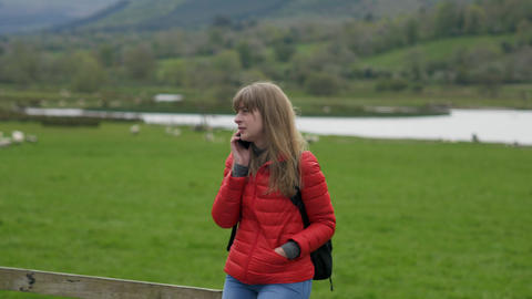 Young woman takes a phone call while standing in a typical Irish scenery Footage