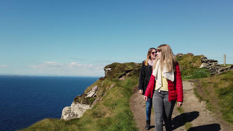 Two girls walk along the edge of the famous Cliffs of Moher Live Action