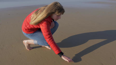Girl writes a heart symbol in the sand on a beach Footage