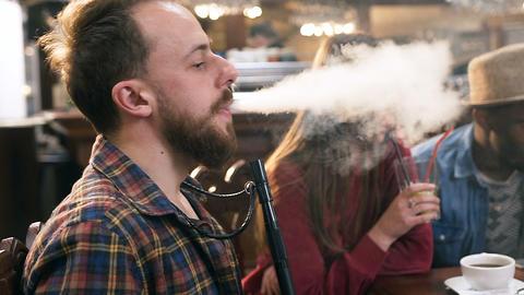 Caucasian young man smoking hookah in the bar Footage