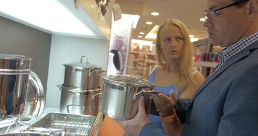 Man and woman buying metal cooking pot in the store Footage