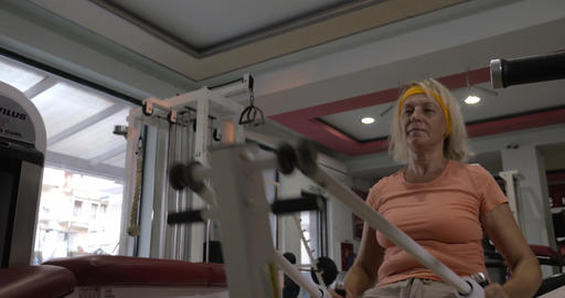 Mature woman exercising on fitness machine Footage