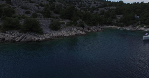 Aerial scene of coastline in a Croatian bay. Detail of catamaran anchored. Drone Footage