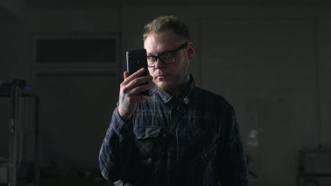Man in glasses watches video on his smartphone in the dark environment, people Live Action