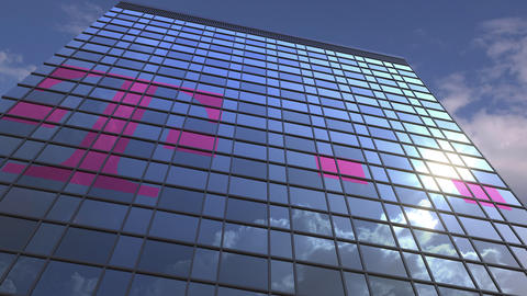 Logo of DEUTSCHE TELEKOM AG on a media facade with reflecting cloudy sky Footage