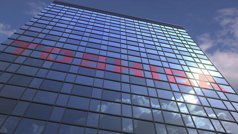 Logo of TOSHIBA on a media facade with reflecting cloudy sky, editorial Live Action