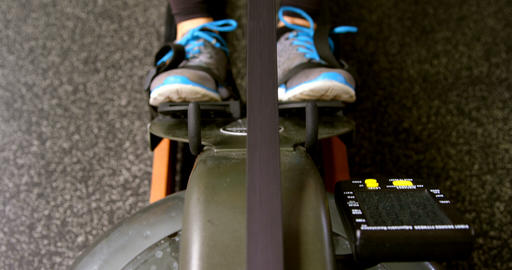 Determined Caucasian woman exercising with rowing machine in fitness studio 4k Live Action
