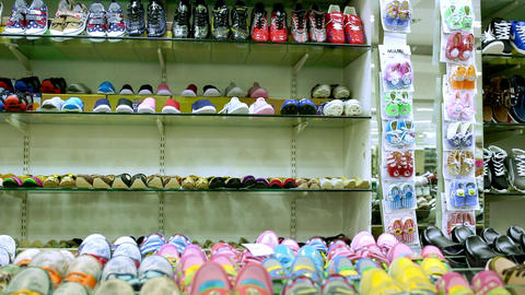Interior of kids store. Racks with kids shoe display wall shelves in children's clothing store Footage