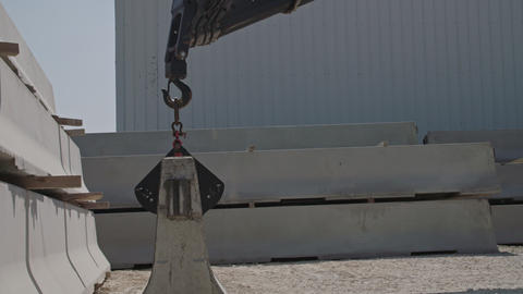 Crane lifting a part of a concrete wall at a construction site Live Action