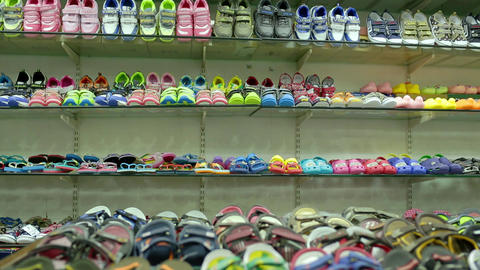 Interior of kids store. Racks with kids Shoe display wall shelves with kids boots and sneakers Footage